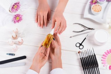 partial view of woman taking aroma oil bottle from hands of manicurist at table with nail polishes, nail files, nail clippers, cuticle pusher, sea salt, flowers, cream and samples of nail varnishes