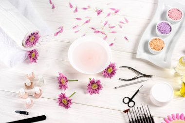 Elevated view of bath for nails at table with flowers, petals, towels, nail polishes, nail file, cuticle pusher, nail clippers, scissors, sea salt, cream container, aroma oil bottles and nail samples of nail varnishes at table stock vector