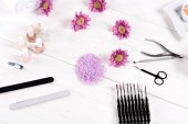 Fotografie top view of of colorful sea salt, towels, flowers, nail polishes, nail clippers, cuticle pusher, scissors, nail files and instruments for manicure at table in beauty salon