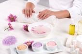 oříznutý obraz ženy držící ruce na ručník pro manikúru postup u stolu s květy, barevné mořská sůl, smetana kontejner, aroma olej láhve a laky na nehty v salonu krásy