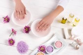 Photo cropped image of woman receiving bath for nails at table with flowers, colorful sea salt, cream container, aroma oil bottles and nail polishes in beauty salon