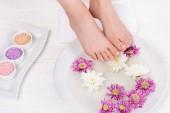 oříznuté záběr bosá žena přijímá lázeň pro nehty s mořskou solí a květiny v salonu krásy