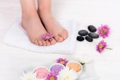 oříznutý obraz bosá žena na lázeňské léčby s ručníkem, květiny, barevné moře soli a wellness kameny