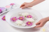 Fotografie cropped shot of woman holding bath for nails with flowers and aroma candles at table in beauty salon