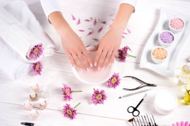 cropped image of woman receiving bath for nails at table with flowers, towels, colorful sea salt, aroma oil bottles, nail polishes, cream container and tools for manicure in beauty salon