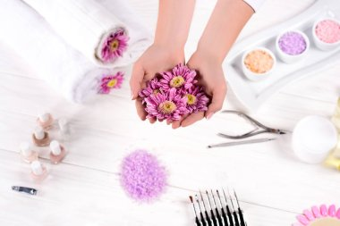 cropped image of woman holding flowers over table with towels, nail polishes, colorful sea salt, cream container and tools for manicure in beauty salon