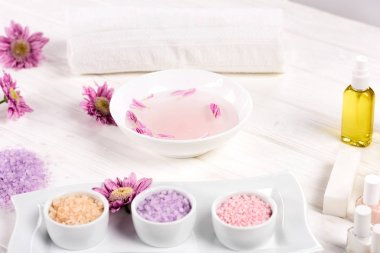 close up shot of bath for nails with petals at table with flowers, towel, colorful sea salt, nail polishes and aroma oil bottle for manicure and pedicure in beauty salon