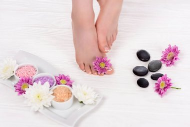 cropped image of barefoot woman on spa treatment with flowers, colorful sea salt and spa stones