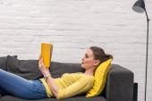 boční pohled na čtení knih vleže na gauči doma dospělé ženy
