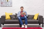 Photo happy adult man reading book on sofa at home