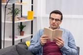 Fotografie Koncentrovaná dospělého jedince knihu na gauči doma