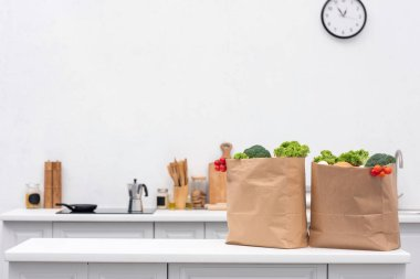 grocery store bags with vegetables on table at kitchen