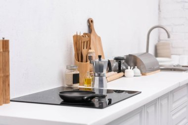 frying pan on induction panel at modern kitchen with various utensils