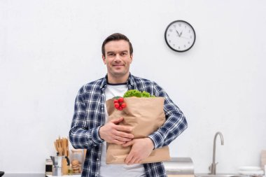 happy adult man carrying grocery store bag at kitchen and looking at camera
