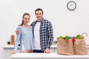 happy adult couple with paper bags from grocery store embracing at kitchen and looking at camera