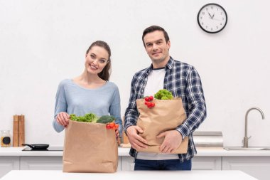 happy adult couple with paper bags from grocery store at kitchen