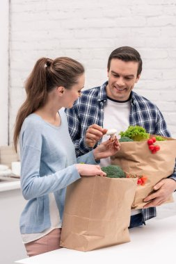 smiling adult couple with paper bags from grocery store at kitchen