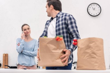 adult man carrying paper bag from grocery store while his wife talking by phone