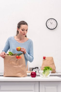 adult woman taking fruits and vegetables out of paper bag at kitchen