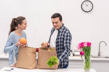 beautiful adult couple taking vegetables and fruits out of paper bags from grocery store