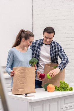 happy adult couple taking vegetables and fruits out of paper bags from grocery store