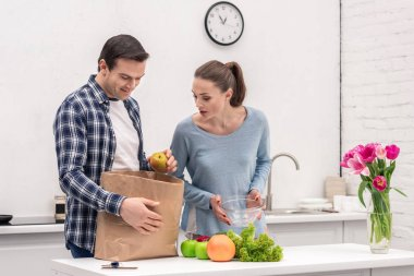 surprised adult couple unpacking paper bag after grocery shopping