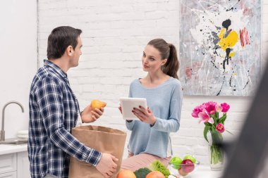 smiling adult couple checking buys list in tablet after grocery shopping