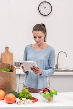 attractive adult woman with tablet checking list of buys after grocery shopping at home