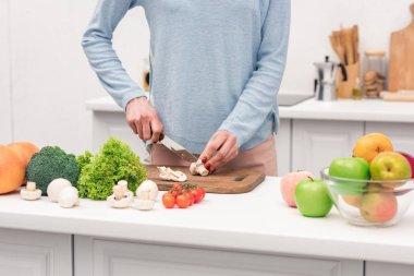 cropped shot of woman cutting mushrooms at kitchen