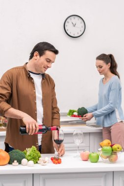 happy husband pouring wine for wife during dinner preparation