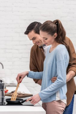 happy husband embracing his wife from behind while she cooking