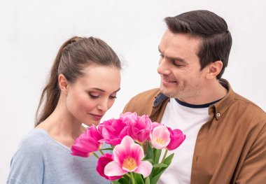 happy adult man presenting tulips bouquet for wife