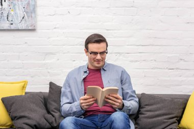 Happy adult man reading book on sofa at home in front of white brick wall stock vector