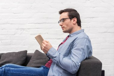 focused adult man reading book on couch at home