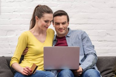 happy adult couple making e-shopping with laptop and credit card on couch at home