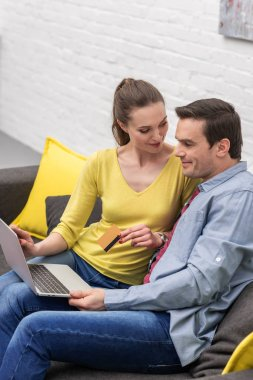 smiling adult couple making e-shopping with laptop and credit card on couch at home