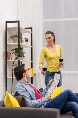 attractive adult woman giving glass of wine to her boyfriend at home