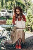 Fotografie elegantní žena s taškou pomocí smartphone při posezení na terase v kavárně