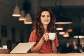 portrait of smiling woman with cup of coffee at table with laptop in cafe
