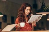 portrét ženy s šálkem kávy, čtení novin u stolu s notebookem v kavárně