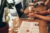 Oříznout záběr blogger, pracují na notebooku s prázdnou obrazovkou v kavárně