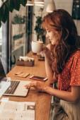 boční pohled mladých blogger s šálkem kávy, pracovat na notebooku v kavárně