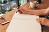vágott szemcsésedik-ból blogger jegyzetelés notebook asztalnál csésze kávét a kávézóban