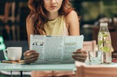 Fotografie částečný pohled ženy, čtení novin v kavárně