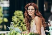 Fotografie boční pohled atraktivní mladá žena v brýlích s novinami v restauraci