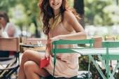 Fotografie částečný pohled podnikatelka sedí u stolu s notebookem v kavárně