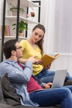 attractive woman with book in hands talking to boyfriend while he work with laptop on couch at home