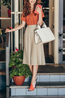 partial view of stylish woman with smartphone and bag walking out cafe