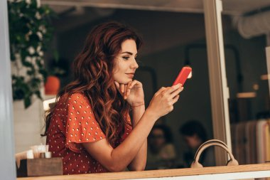 side view of young woman using smartphone in cafe
