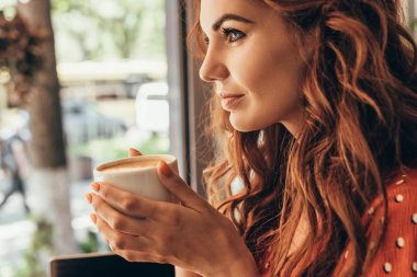 side view of pensive woman with cup of aromatic coffee in cafe